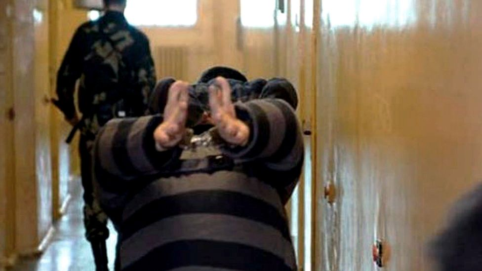 Prisoner walks handcuffed inside a prison in Minsk in 2006