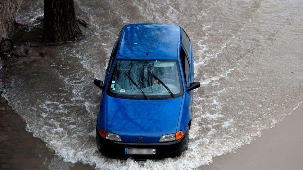 Автомобиль едет по затопленной улице