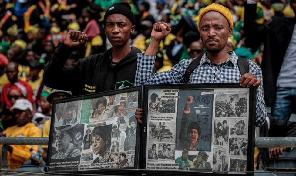 Mourners with raised clinched fists stand watching from the stands of the full 37,500-seater Orlando Stadium, in the township of Soweto, the funeral of the late anti-apartheid champion Winnie Madikizela-Mandela, concluding 10 days of national mourning on April 14, 2018, in Johannesburg. South Africans turned out in their thousands to bid final goodbyes to anti-apartheid icon and Nelson Mandela's former wife who was laid to rest with full state honours. Winnie Mandela, who died in Johannesburg aged 81 on April 2 after a long illness, has been celebrated for helping keep Nelson Mandela's dream of a non-racial South Africa alive while he was behind bars for 27 years.