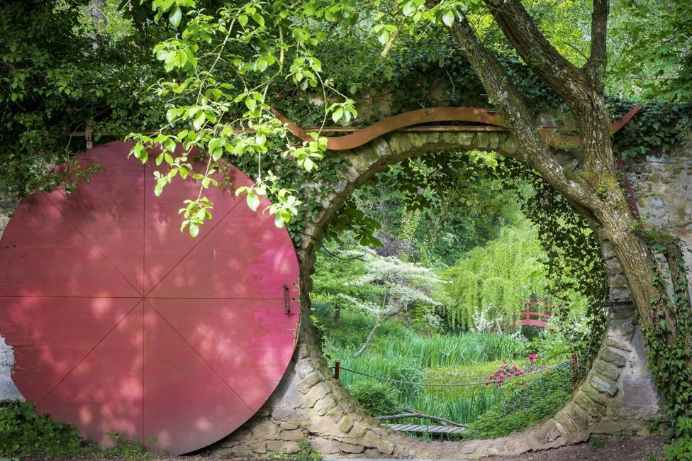 Un puerta circular tras la cual hay un jardín.