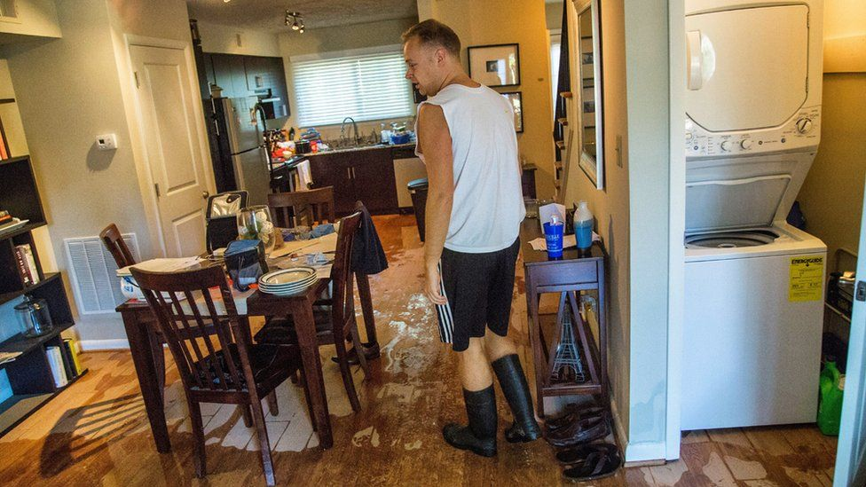 Jeremy Spearman checks on flood damage to his Parkside Five Points Townhomes apartment in Raleigh, N.C., after Hurricane Matthew caused downed trees and flooding Sunday, Oct. 9, 2016