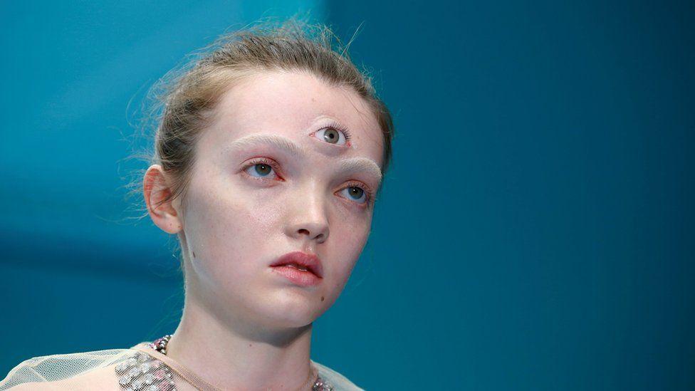 Modelo femenino con un tercer ojo protésico unido a su frente