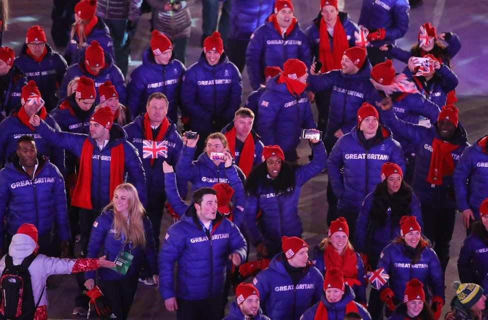Team Great Britain athletes walk holding flags and recording on their phones