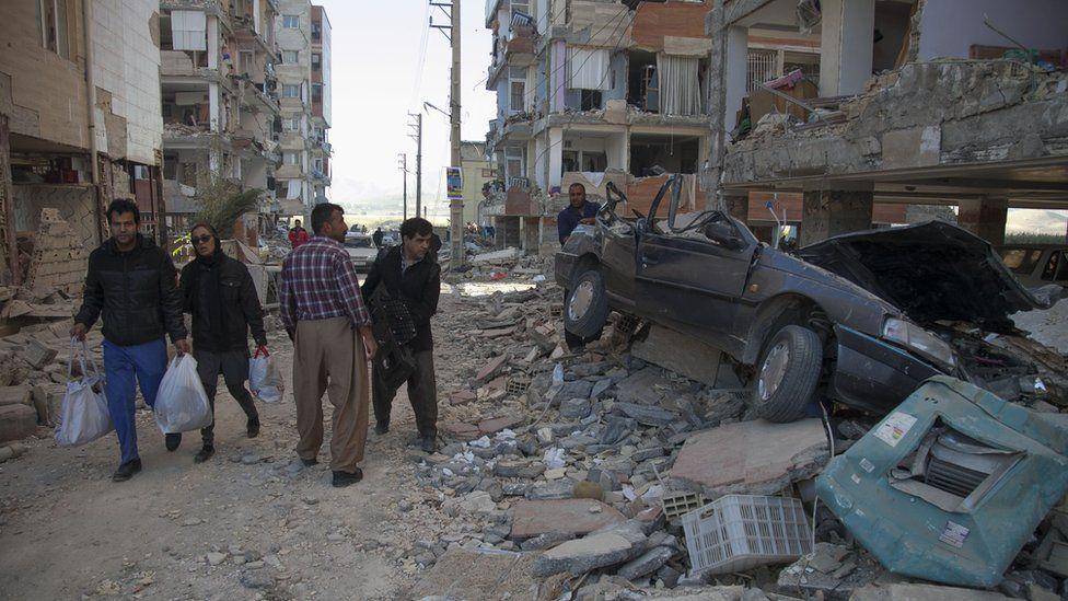 Transeúntes observan los destrozos y escombros dejados por el terremoto en Irán