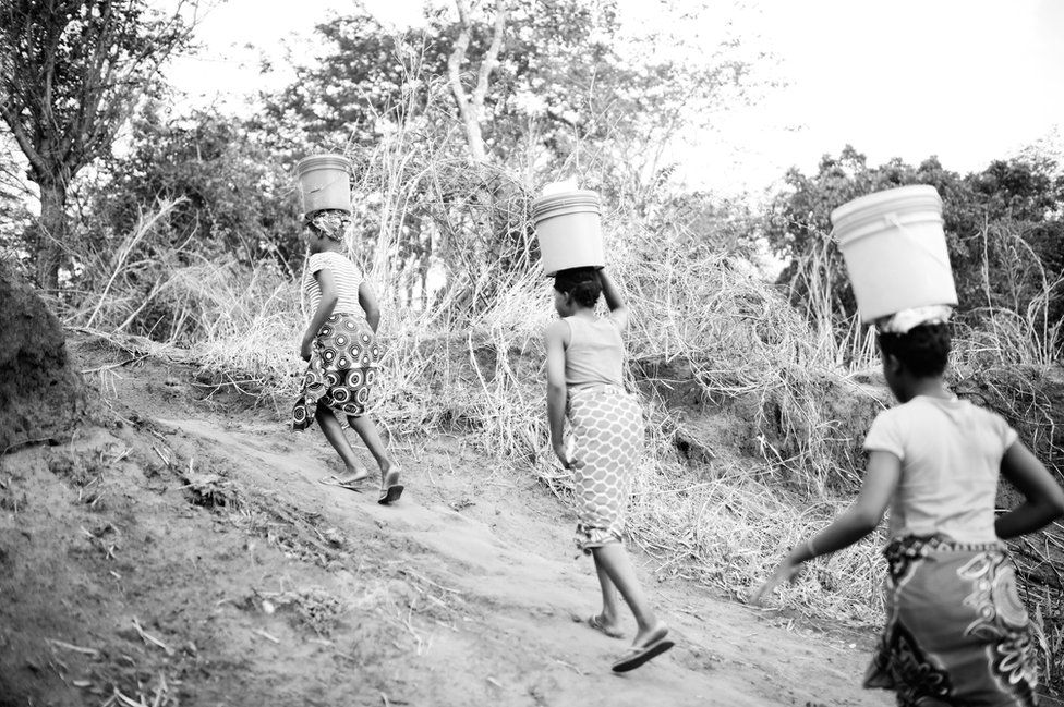Josefina and Eudicia climb a hill with buckets balanced on their heads.