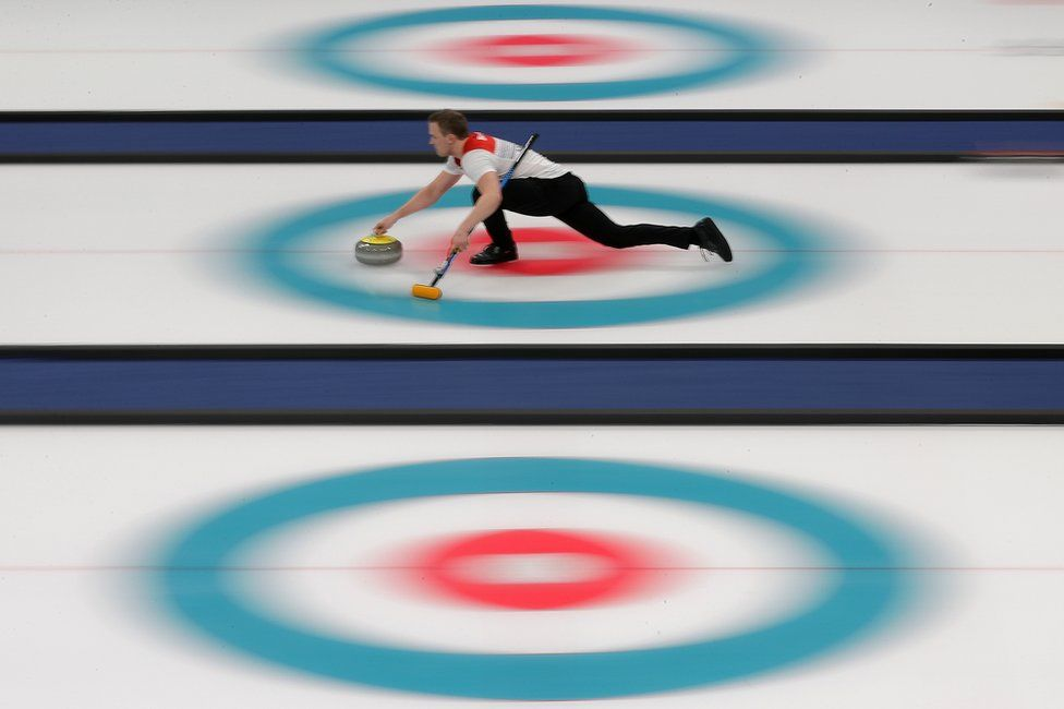 Magnus Nedregotten slides along the ice whilst Curling