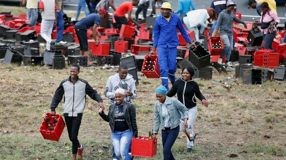 People carrying crates of beer away from a truck, near Johannesburg, South Africa - Friday 29 September 2017