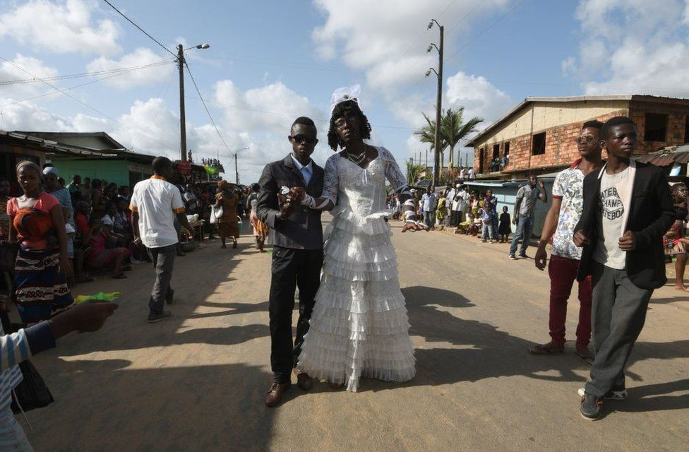 Men from the ethnic southeastern Aboure people, dressed up as a bride and groom, pose for a photograph during the 38th Edition of the POPO Carnival of Bonoua, 50 kms east of Abidjan, an annual festival held by the Aboure people on April 14, 2018.