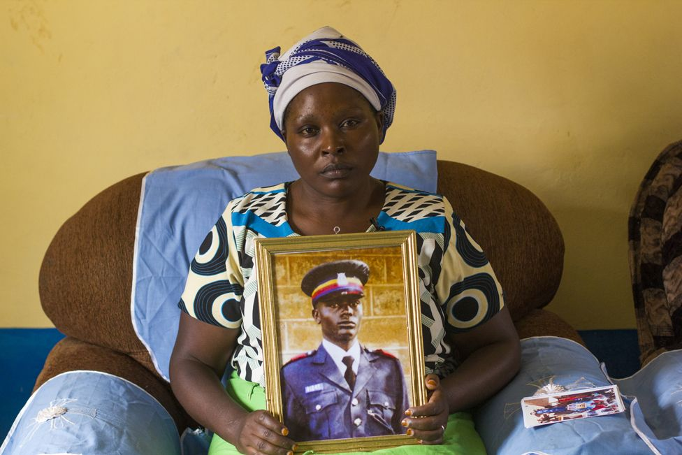 Irene Nduku Kasyoki holds up a portrait of her late husband Geoffrey Kasyoki, a police officer who died trying to save his community's sand