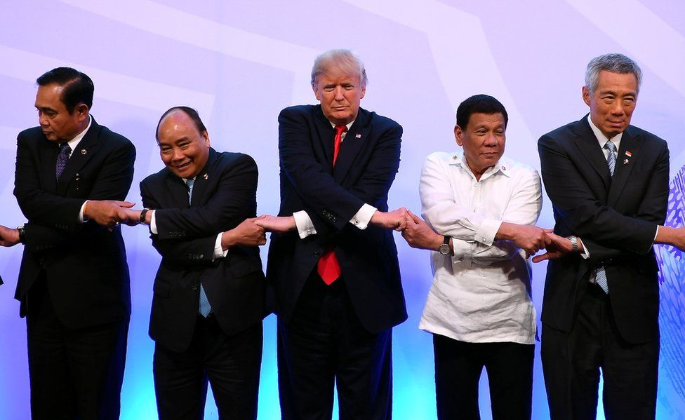 President Donald Trump holds hands with a row of leaders.