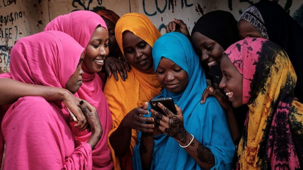 Young Somali refugee women look at a smartphone as they stand together at Dadaab refugee complex, in the north-east of Kenya, on April 16, 2018. The Dadaab refugee complex which has some 235269 refugees and asylum seekers in four camps about 80kms from the Somali-Kenyan border was established in 1991, according to UNHCR camp population statistics in January 2018.