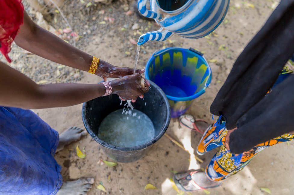 A woman washes her hands with soap and water in Norandé