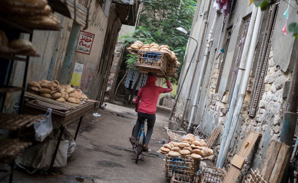 An Egyptian man carries a wood rack full of bread near a traditional bakery in Al Sayeda Zainab district, Cairo, Egypt, 22 November 2017