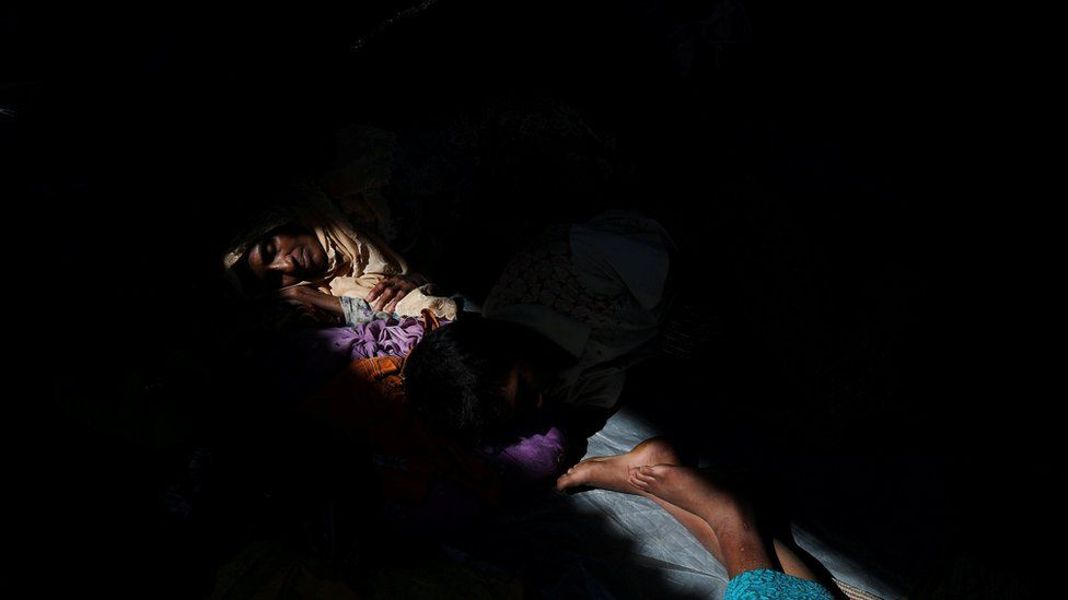 Rohingya refugee Almor Yhan, 59, rests with relatives hours after crossing the Bangladesh-Myanmar border near Cox's Bazar, Bangladesh