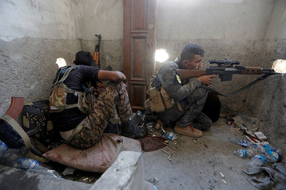 A sniper holds up his weapon.