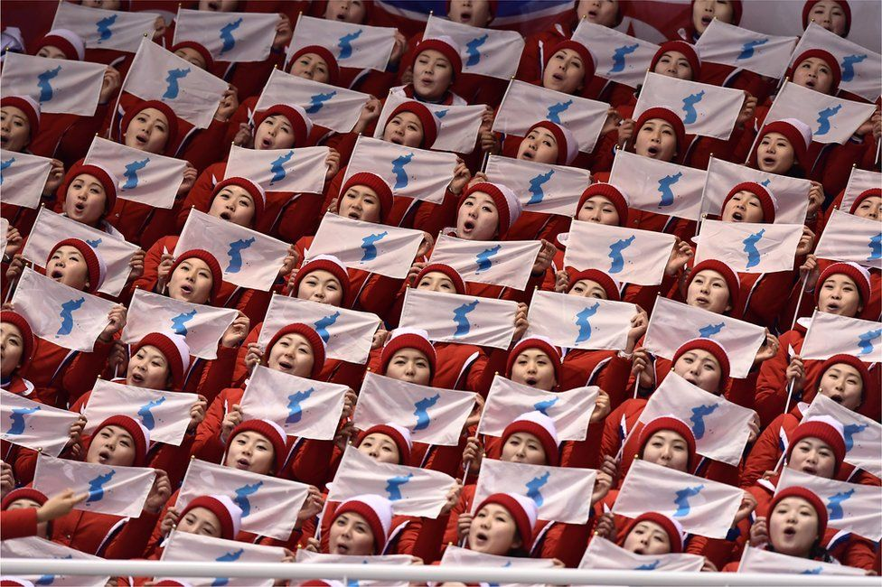 North Korean cheerleaders hold unification flags