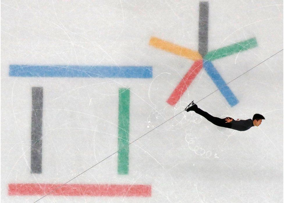 Skater Nathan Chen is seen with arms outstretched with coloured Olympic signs in the ice beneath him