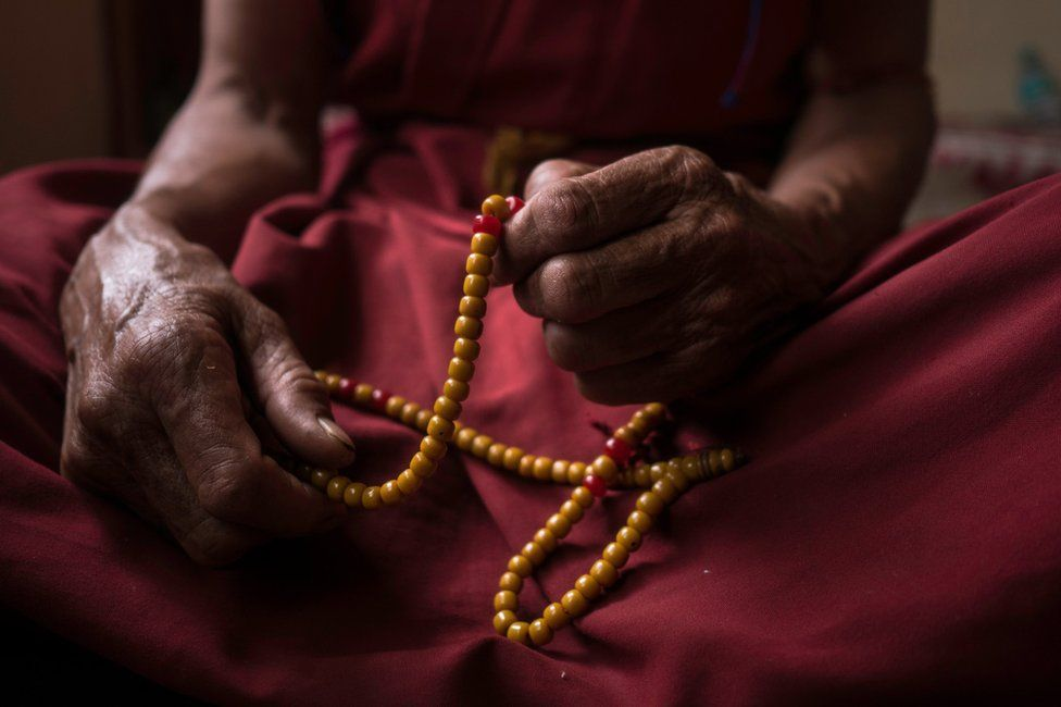An elderly nun holds prayer beads
