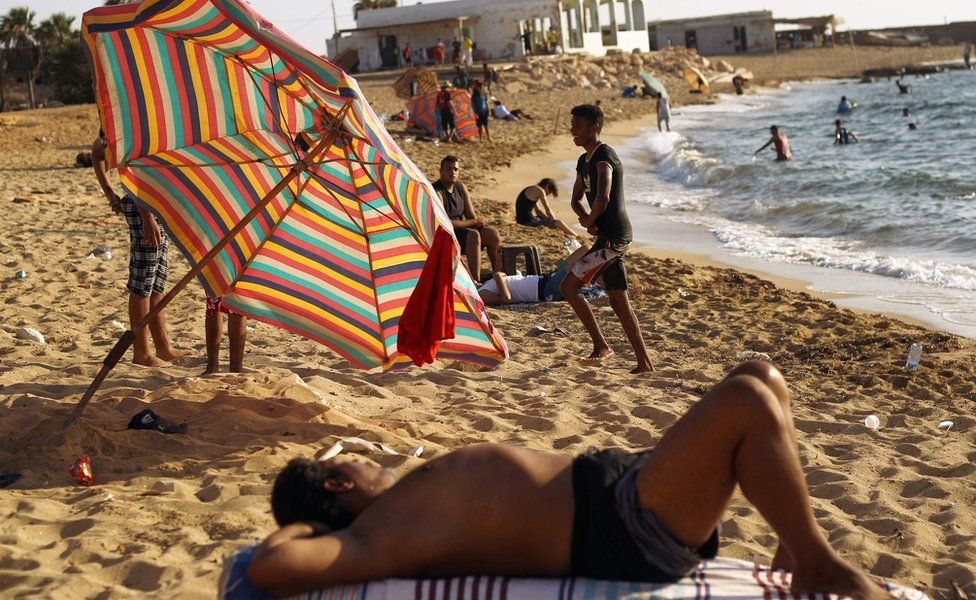 Libyans lying on a beach with others swimming in Benghazi, Libya - Tuesday 6 September 2016