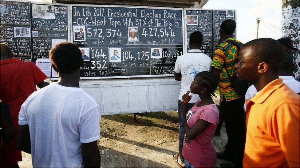 Liberians read from a 'Daily Talk' chalkboard by a roadside in Monrovia, Liberia. 17th October 2017. Liberians who can not afford to buy a newspaper, get information from a public chalkboard and the results of the just ended Presidential and General elections.