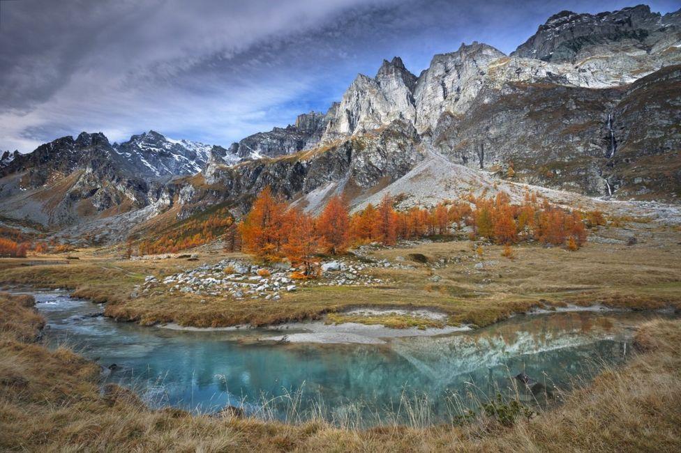 Paisaje montañoso y rocoso con un río y árboles de naranja.