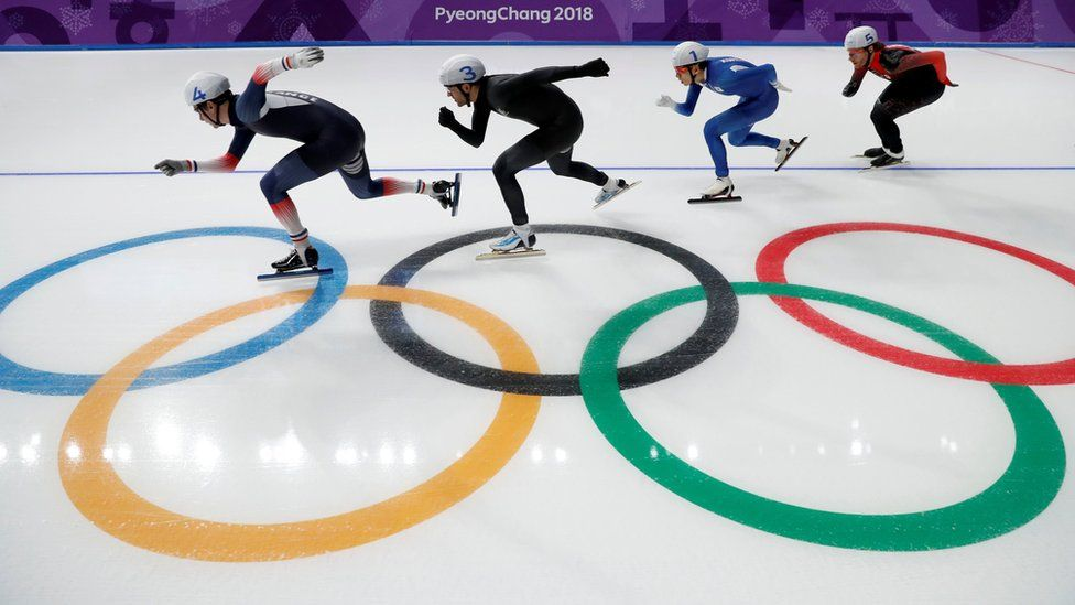 Four male skaters race each other with the Olympic rings image seen in the ice beneath them
