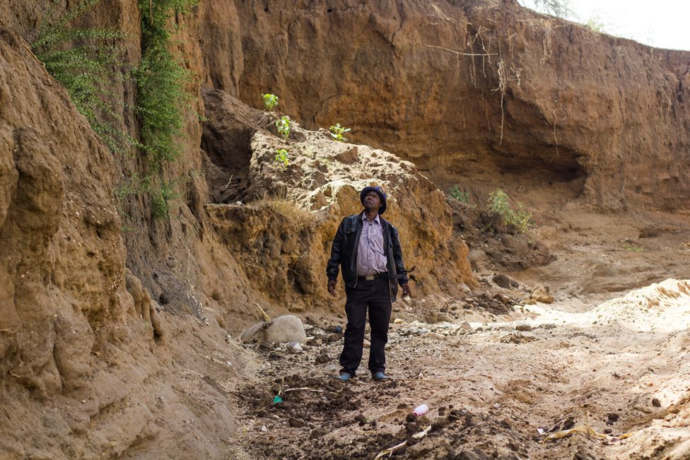 "Anthony Mua Kimeu stares at the steep cliffs of the Kilome Ikolya ""dead"" River"