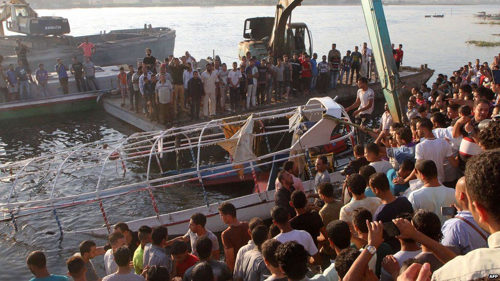 Relatives and onlookers gather on the bank of the Nile on 23 July 2015, as the wreckage of a boat is pulled out of the water