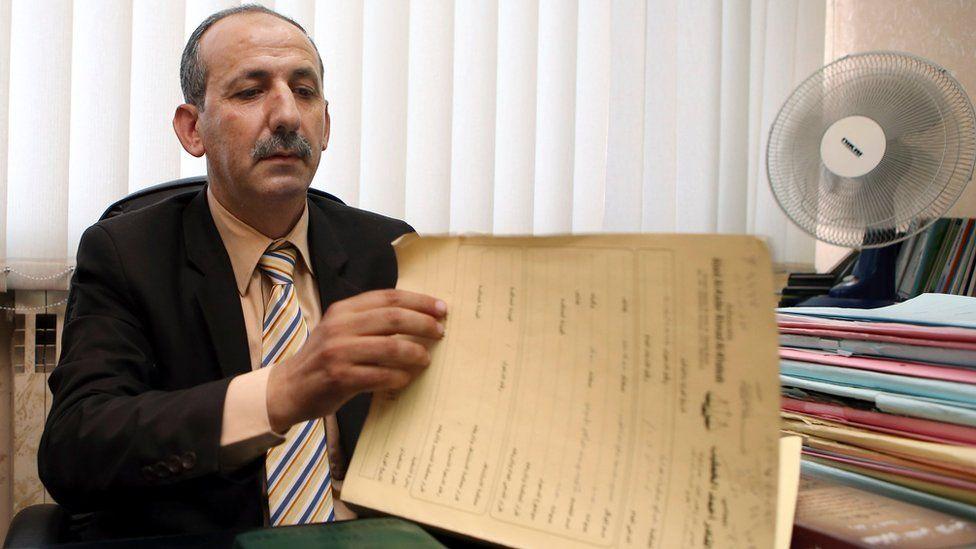 Abed al-Kader Ahmad al-Khateeb looking at papers