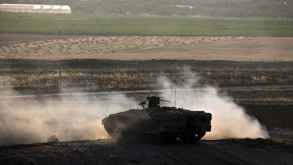 An Israeli armoured personnel carrier manoeuvres on the Israeli side of the border fence between Israel and the Gaza Strip