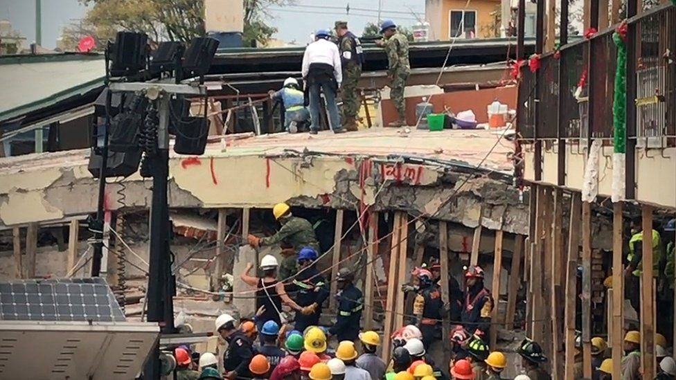 Rescuers ask a teacher (centre, with white helmet) to help communicate with a young girl they believed was trapped alive inside, Mexico City, 20 September 2017