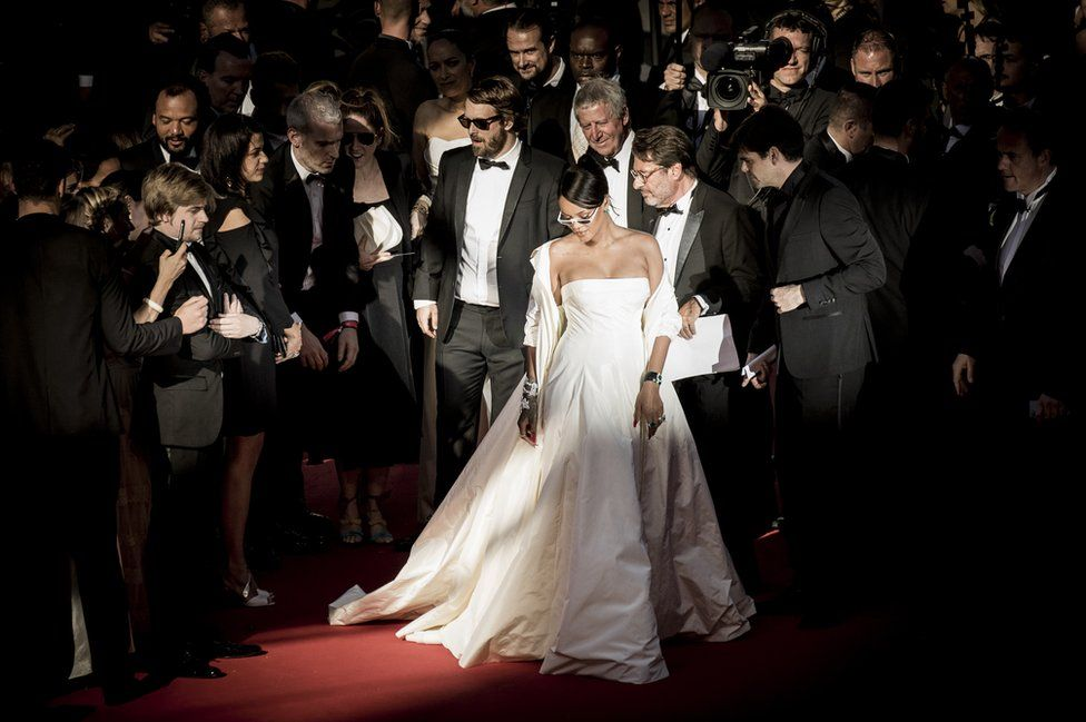 Rihanna looks down on the red carpet.