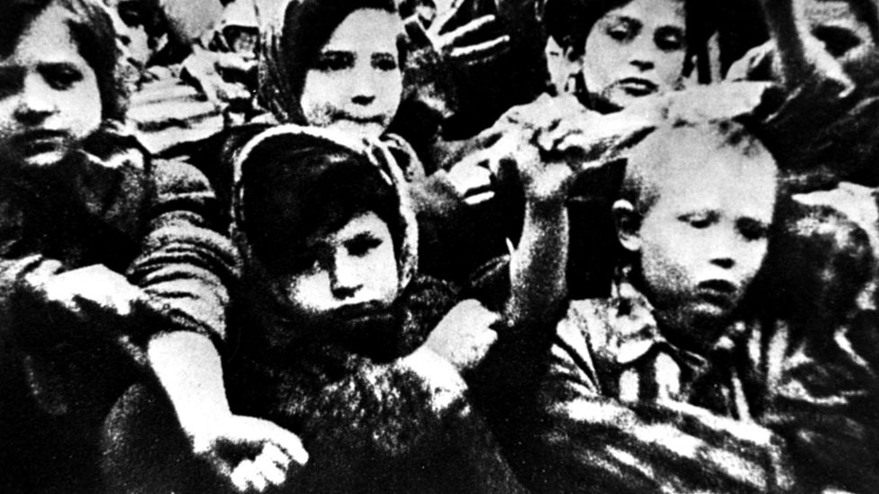 Children of Auschwitz show their tattooed arms