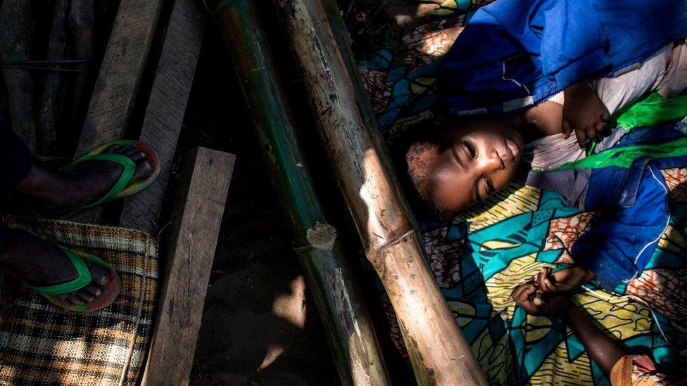 Menino descansa junto com outras pessoas desalojadas em Kikwit, na provîncia de Kasai