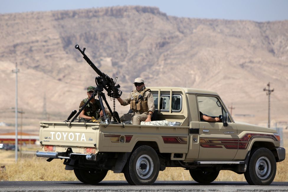 Iraqi Kurdish Peshmerga fighters drive a truck with a machine gun mounted on the back as they head to the Mosul dam on the Tigris river that they recaptured from Islamic State jihadists on August 17, 2014