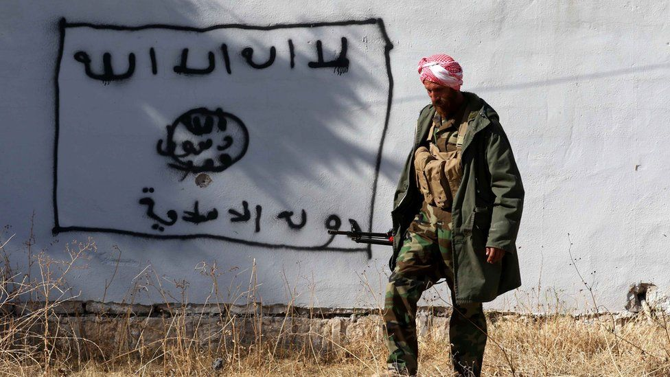 A Kurdish fighter walks by a wall bearing a drawing of the flag of the Islamic State (IS) group in the northern Iraqi town of Sinjar, in the Nineveh Province, on November 13, 2015