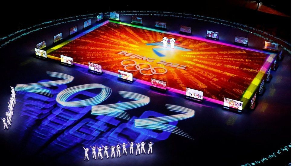 Figures gather around a giant projected logo of the Beijing 2022 Olympics