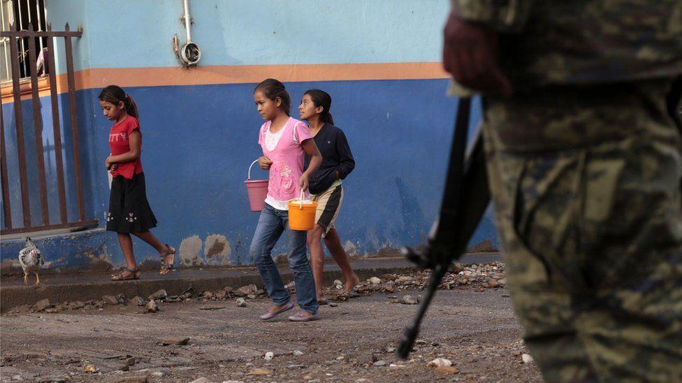 Kızlar, 3 Ağustos 2013'te Meksika'nın Guerrero Eyaleti, Heliodoro Castillo belediye başkanı Huatla kasabasında yürürken askerler tarafından eşlik ediliyor