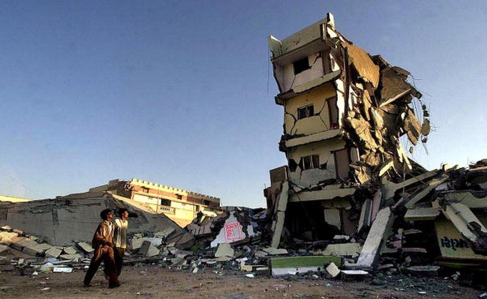 A couple of passersby look at a destroyed building 29 January 2001 where they used live in the town of Bhuj, in Gujarat state, which along with the entire northwestern India was hit by a massive earthquake 26 January.