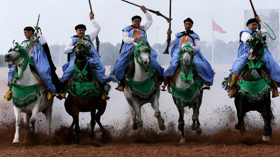 Traditional Moroccan knights ride in an equestrian show during the Festival of Tbourida, a competition between the Moroccan tribes, in Al-Jadidah, Morocco, 18 October 2017. Tbourida is a traditional exhibition of horsemanship in the Maghreb performed during cultural festivals and to close Maghrebi wedding celebrations. The performance consists of a group of horse riders, all wearing traditional clothes, who charge along a straight path at the same speed so as to form a line, the pickup speed and then at the end of the charge, fire into the sky using old muskets or muzzle-loading rifles