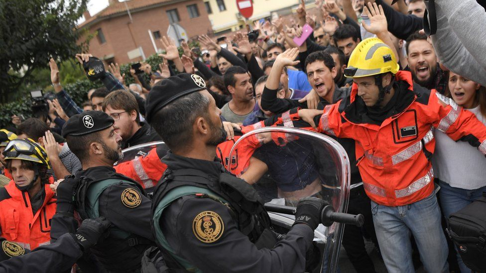Firemen try to hold a group of people in front of Spanish Guardia Civil officers outside a polling station in San Julia de Ramis, on October 1, 2017, on the day of a referendum on independence for Catalonia banned by Madrid.