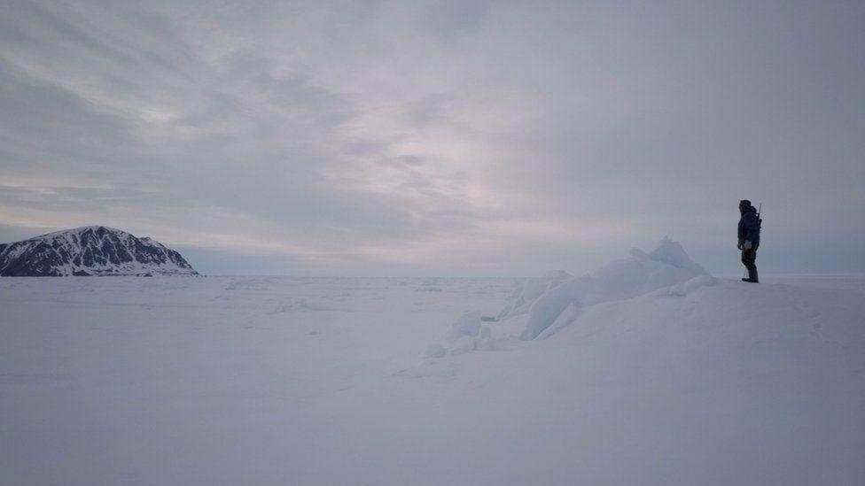 Un hombre de pie en la nieve.