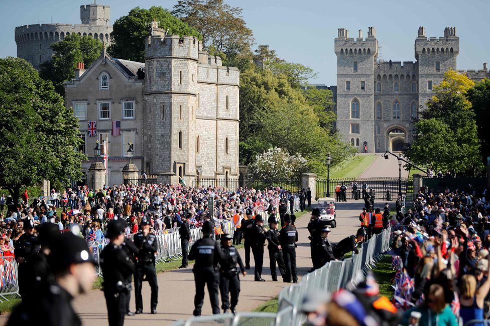 Доброжелатели собираются вдоль длинной прогулки, ведущей в Виндзорский замок перед свадьбой и каретным шествием британского принца Гарри и Меган Маркл в Виндзоре