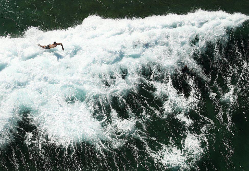 A surfer falls into a wave