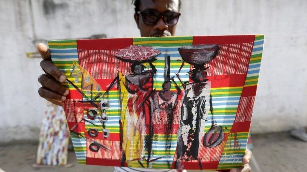 Street artist Lia Annickson showed off one of his paintings in Abidjan, Ivory Coast on Wednesday.