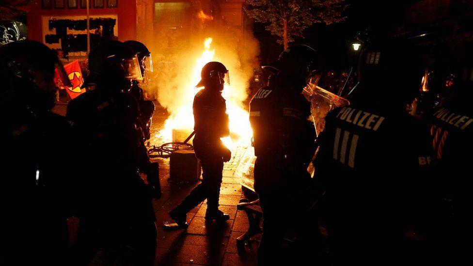Policías junto a un fuego circulando en la noche.