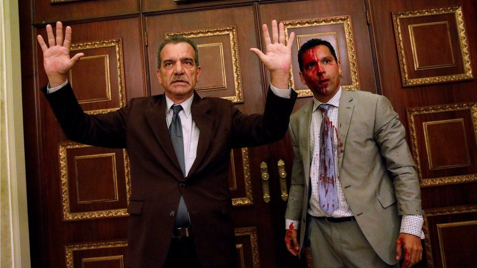 Opposition lawmaker Luis Stefanelli (L) gestures next to fellow opposition lawmaker Leonardo Regnault after a group of government supporters burst into Venezuela's opposition-controlled National Assembly during a session, in Caracas