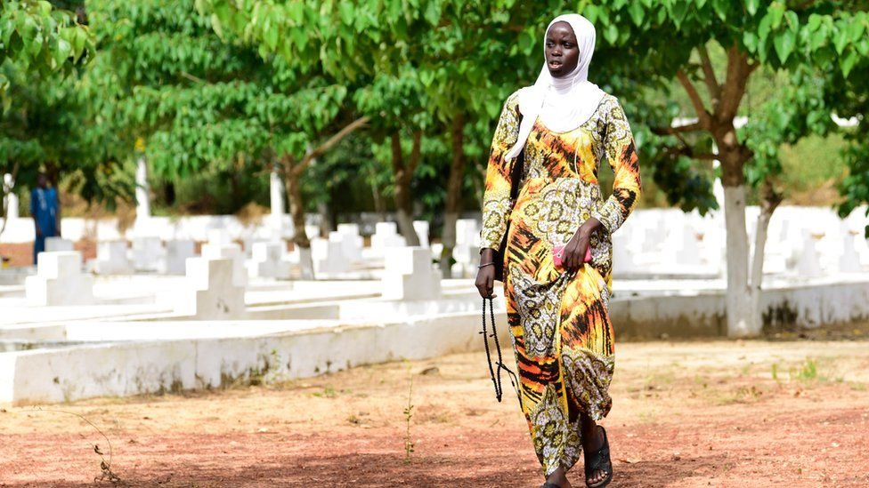A Senegalese woman walks past graves as family and friends visit to mark the 15th anniversary of the sinking of the ship 'Le Joola'