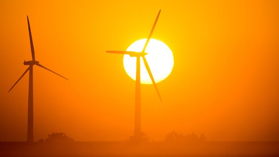 The sun rises behind wind turbines in Mallnow, eastern Germany on August 20, 2015.