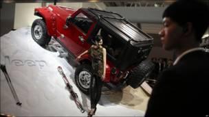 Una modelo posa en frente de un Jeep Wrangler